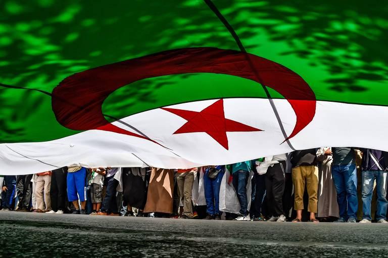 Manifestantes marcham com bandeira da Argélia durante protesto na capital