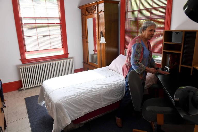 Susan Mitchell arruma cama de quarto de Airbnb antes de clientes chegarem