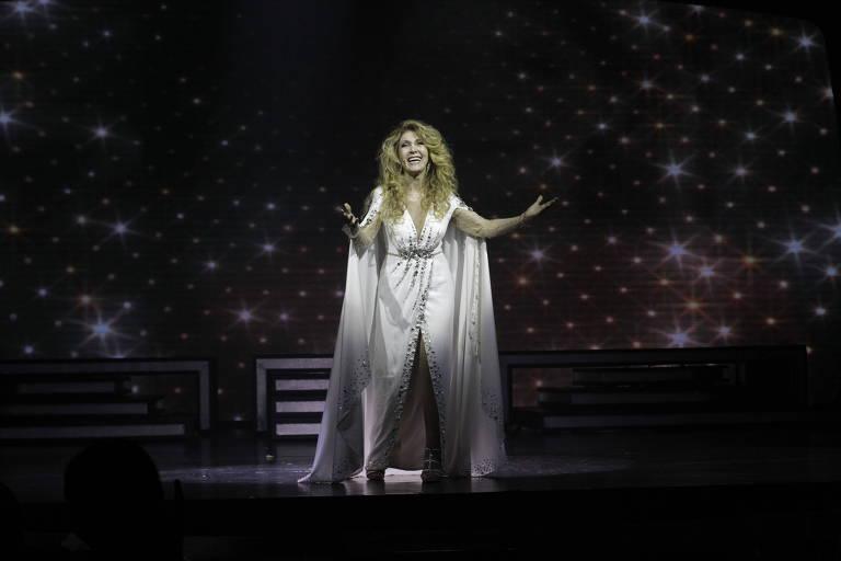 Cantora Wanderléa no espetáculo musical  '60! Década de Arromba', no Teatro Net, em São Paulo. Sozinha no palco, ela veste uma roupa inteiramente branca e está com ambos os dois braços abertos