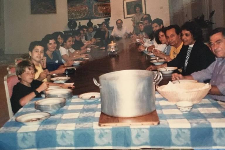 Pessoas sentadas em uma mesa com um panelão na frente