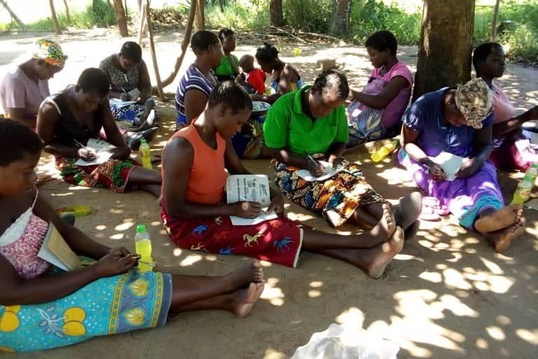 Várias mulheres do Malaui sentadas no chão desenham em caderno