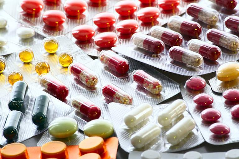 Diferentes tipos de remédios coloridos dentro de embalagens prateadas com parte superior transparente