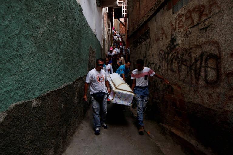 Familiares carregam caixão com o corpo de Erick Altuve, 11, que morreu devido a problemas respiratórios durante tratamento para câncer em Caracas