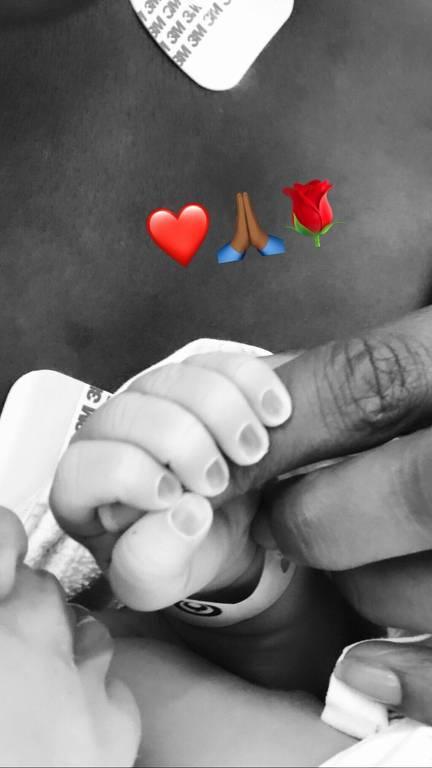 mão do bebê segurando dedo da mãe