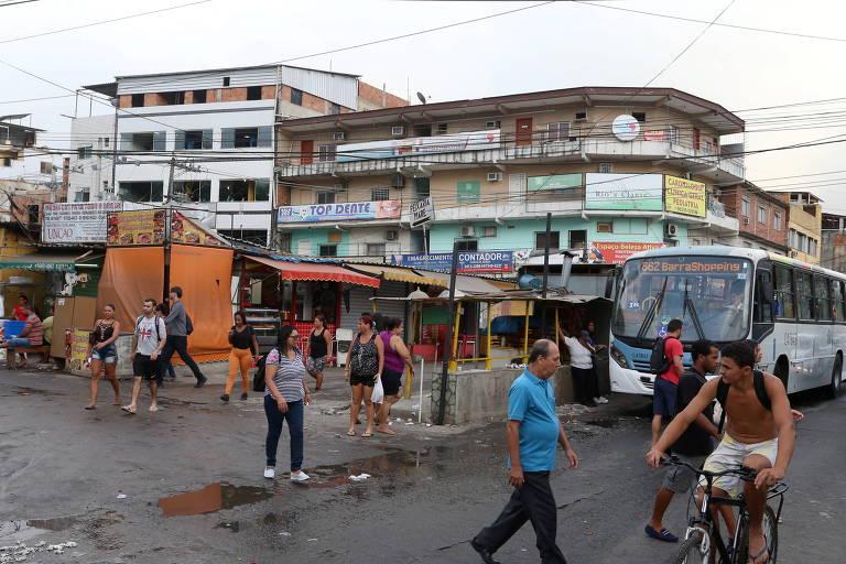 Vista de praça com camelôs e transeuntes em comunidade carioca, em dia nublado, com ônibus à direita