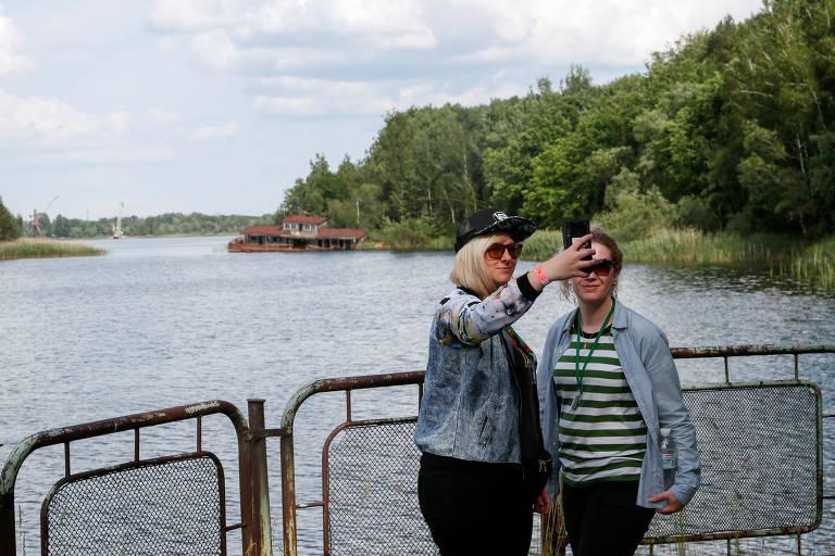 Turistas tiram fotos em um rio abandonado na cidade de Pripyat, próxima a Chernobyl