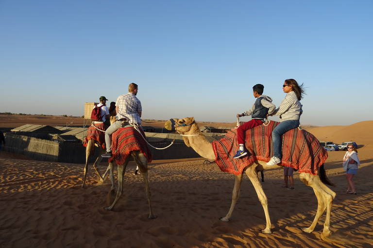 Passeio de camelo no deserto de Dubai, nos Emirados Árabes