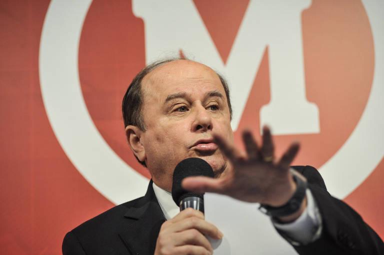 benedito fala ao microfone com a mão estendida para frente. No fundo, símbolo do Mackenzie