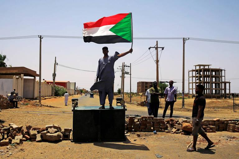 Manifestante sudanês com a bandeira nacional em uma barricada em Cartum
