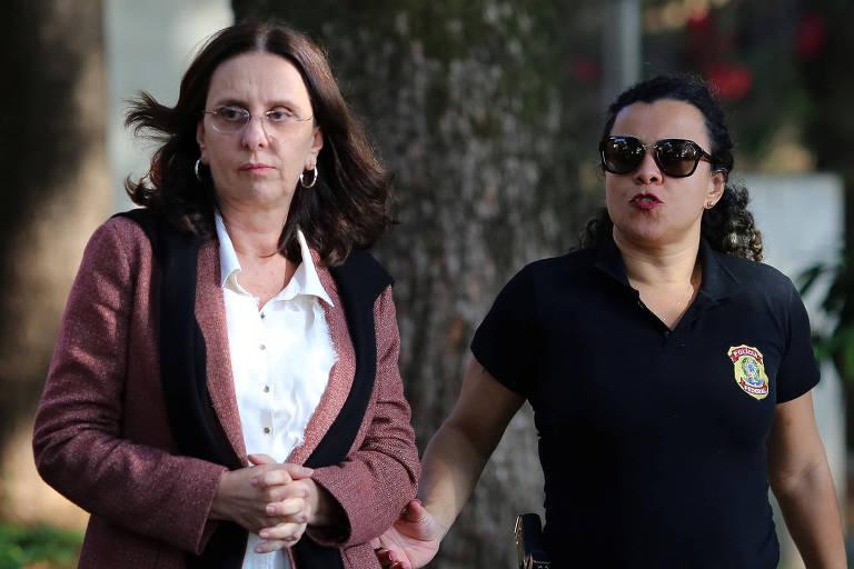 Retrato de Andrea Neves (esq.) e uma oficial da Polícia Federal (dir.); Andrea usa um caso rosa millennial com detralhes em preto, uma camisa branca. usa óciulos e tem cabelo castanho escuro e longo. A oficial usa uma camisa polo preta com o logotipo da PF no lado esquerdo