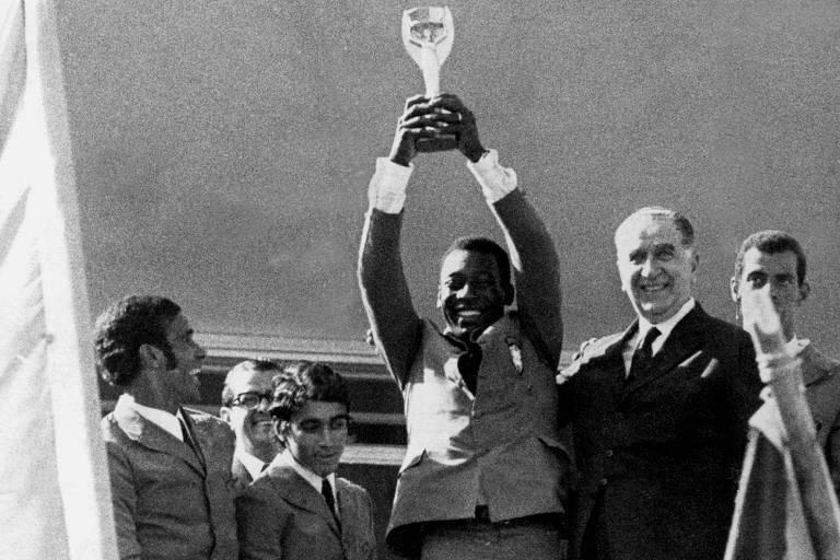 Pelé levanta a Taça Jules Rimet, conquistada no México, ao lado de Emílio Garrastazu Médici
