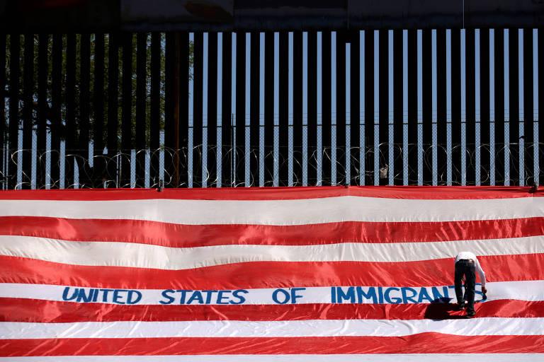 """Roberto Marques, ativista conhecido como Roberz, escreve """"Estados Unidos de Imigrantes"""" na bandeira estadunidense enorme, estendida no lado mexicano do """"muro de Trump"""" contra a imigração, como parte de um protesto que exigiu respeito aos migrantes, próximo ao muro na fronteira de El Paso, Texas. A foto foi tirada na Cidade de Juarez, Mexico, em 6 junho de 2019."""