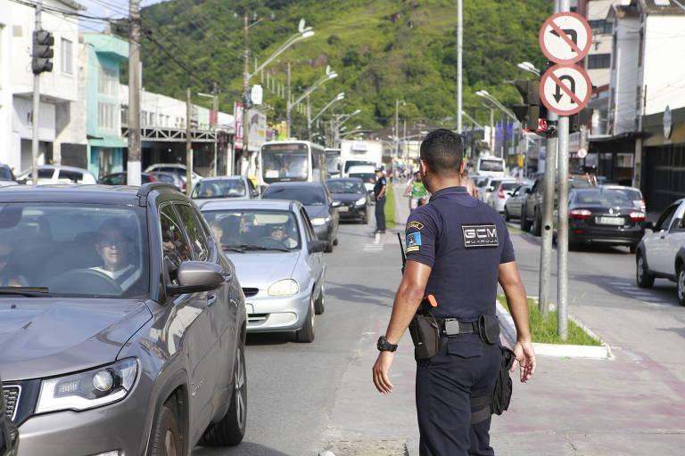 Guarda fiscaliza carros na fila da balsa entre Santos e Guarujá, no litoral paulista