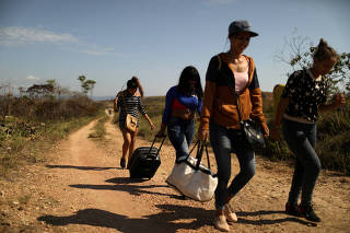 FILE PHOTO: Venezuelan migrants walk along a trail into Brazil in the border city of Pacaraima