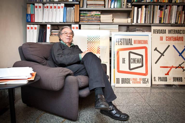 O design Alexandre Wollner, sentado em uma poltrona em sua casa. Ao fundo, há estantes com livros e cartazes que ele fez para a Bienal e para as comemorações dos 400 anos de São Paulo