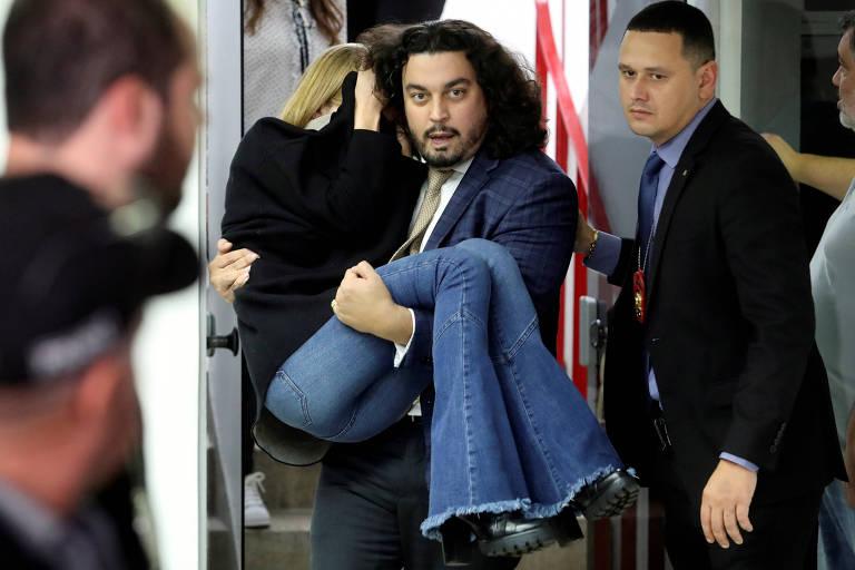 Najila Trindade de Souza é a carregada por seu advogado, Danilo Garcia de Andrade, após passar mal durante depoimento à Polícia Civil