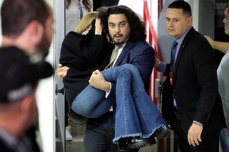 O advogado Danilo Garcia de Andrade carrega a modelo Najila Trindade de Souza após ela passar mal durante depoimento à Polícia Civil em São Paulo
