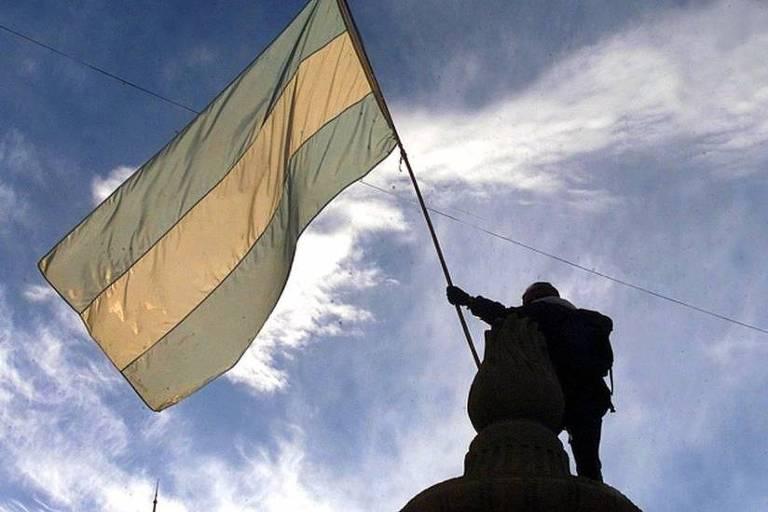 Homem segurando uma bandeira da argentina com céu azul ao fundo