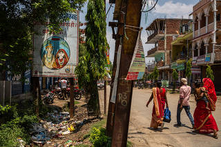 Pedestrians walk by a billboard warning against child marriage in the southern district of Saptari, Nepal.