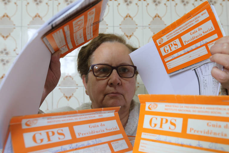 A dona de casa Sandra Regina da Silva, 60 anos, mostra os seus carnês de contribuição para a Previdência Social