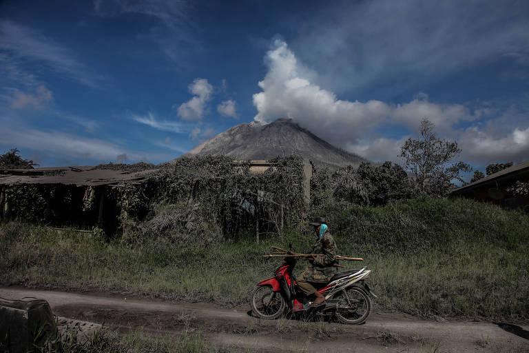 Homem trafega de moto próximo ao vulcão