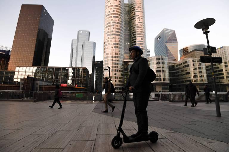 Homem em patinete elétrica no distrito financeiro de Paris