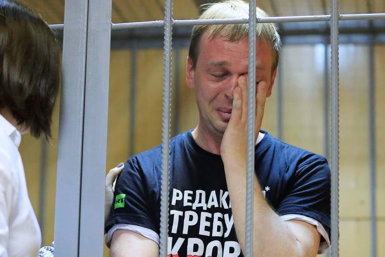 """Golunov chora em audiência durante prisão em Moscou, vestindo uma camiseta que diz """"Redação demanda sangue"""""""