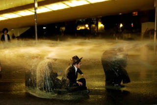 FILE PHOTO: Israeli ultra-Orthodox Jewish men sit as a water canon is activated during a protest against the detention of a member of their community who refuses to serve in the Israeli army, in Jerusalem
