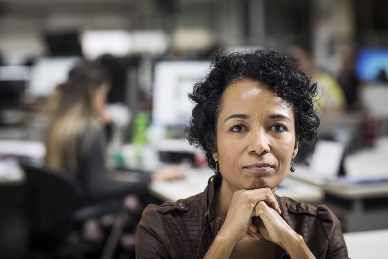 Flavia Lima, ombudsman da Folha, apoia o queixo nas mãos e olha para a câmera. Ela veste um casaco marrom e está na redação, com outros jornalistas e computadores ao fundo.