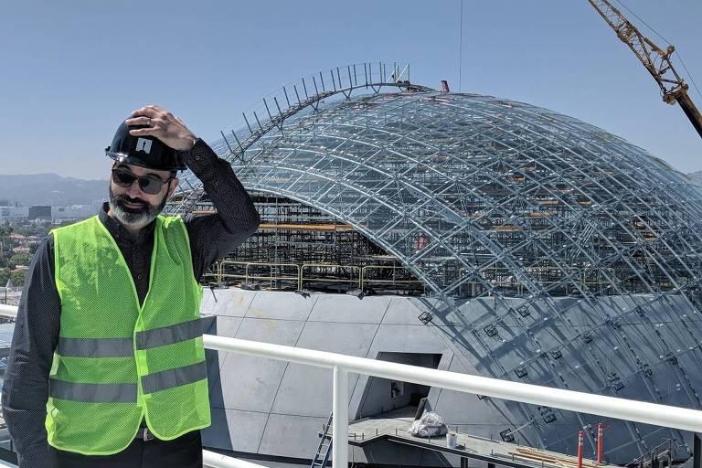 homem em construção, de capacete, óculos escuros e colete amarelo