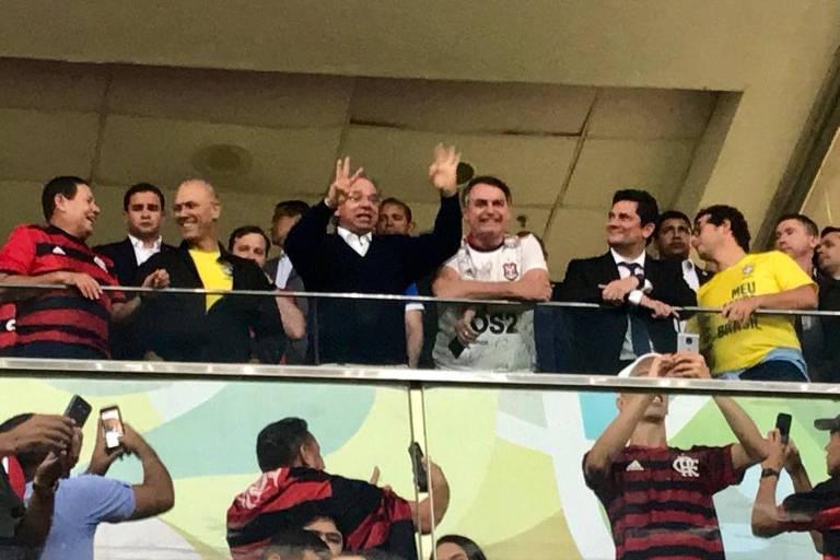 Hamilton Mourão, Paulo Guedes, Jair Bolsonaro e Sérgio Moro, da esquerda para a direita, estão em uma tribuna do estádio Mané Garincha, em Brasília. Abaixo deles, torcedores tiram fotos.