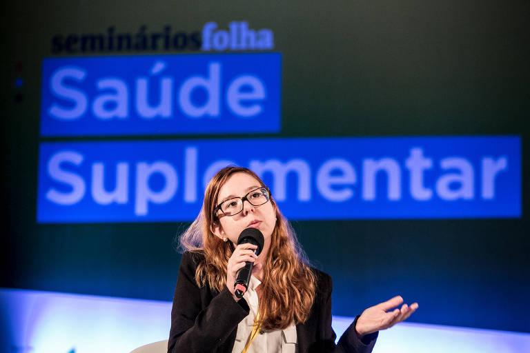 Mulher ao centro, com microfone na mão; ao fundo, painel onde se lê Saúde Suplementar