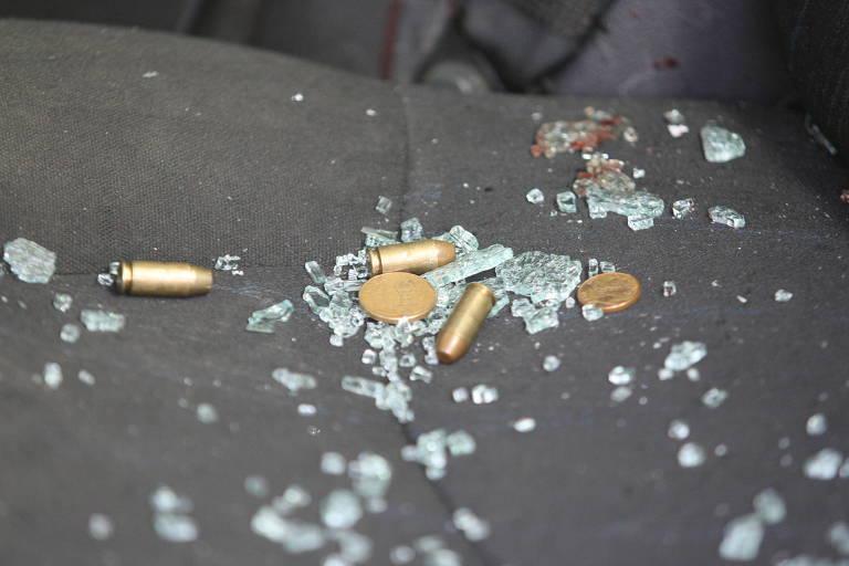 cacos de vidro e cartuchos de bala sobre banco ce carro