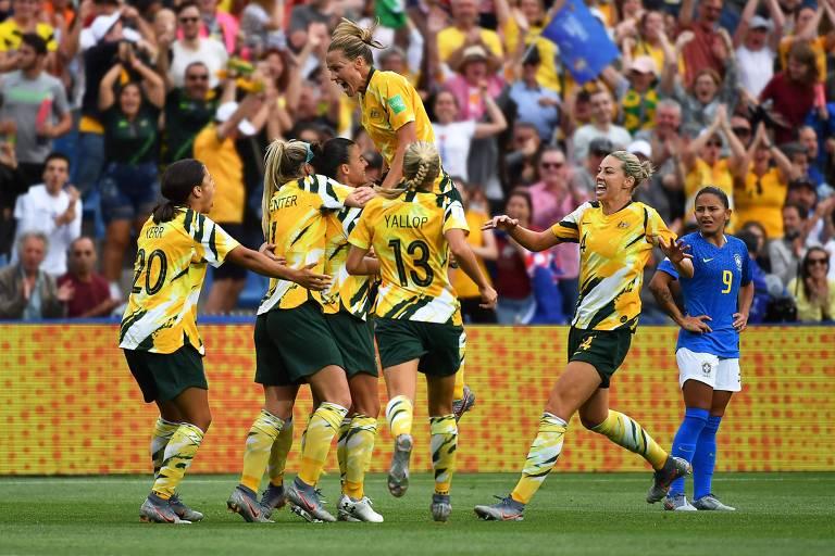 Jogadores australianas se abraçam, enquanto atleta do Brasil aparece ao fundo com as mãos na cintura