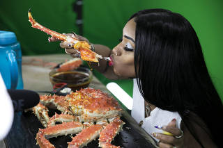 Bethany Gaskin eats a king crab on camera as part of a Youtube Mukbang challenge in Mason, Ohio.