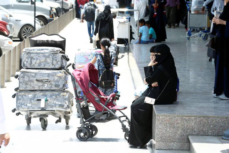 Mulher de burca preta aguarda sentada em mureta; a sua frente, carrinho com três malas grandes