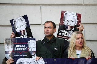 Demonstrators hold placards as they protest outside of Westminster Magistrates Court, where a case hearing for U.S. extradition of Wikileaks founder Julian Assange is held, in London