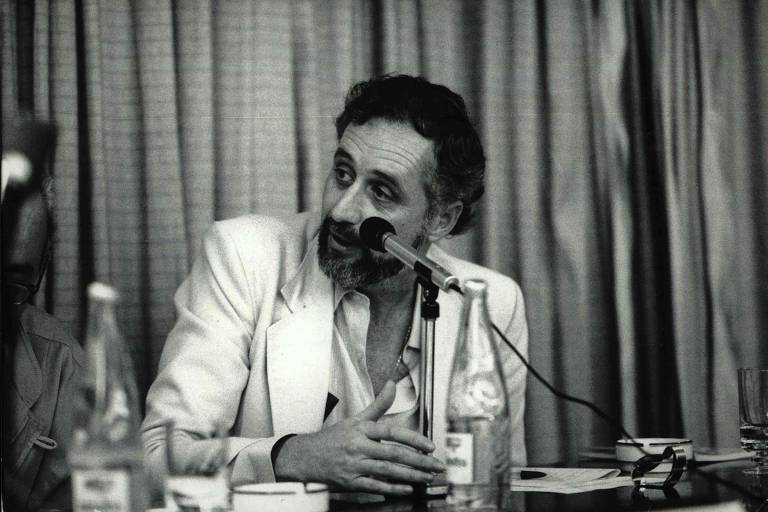 retrato em preto e branco de homem branco de barba e cabelos grisalhos fala ao microfone sentando em uma mesa