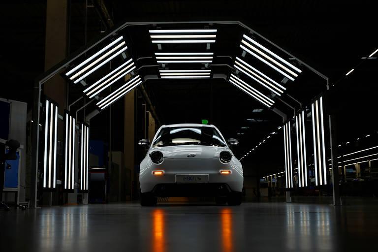Carro elétrico desenvolvido na Alemanha cercado por ambiente escuro e com algumas luzes o destacando