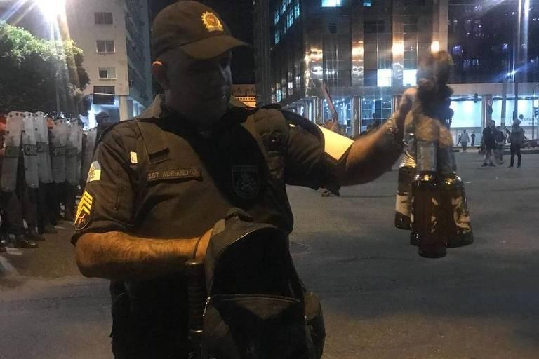 Policial militar mostra coquetéis molotov que diz ter achado em mochila de manifestante que estaria correndo