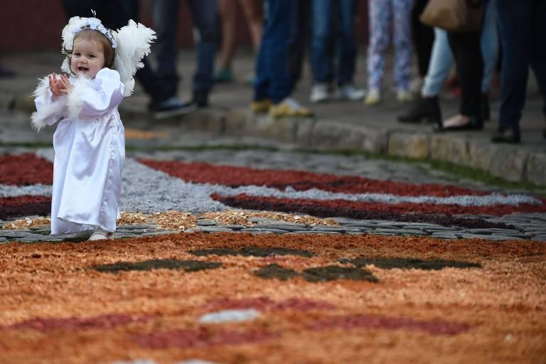 Criança vestida de anjo, à esquerda, passeia sobre tapete de Corpus Christi