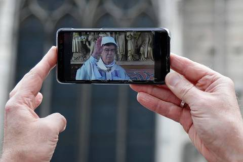 A man holds a smartphone showing a live broadcast of Archbishop of Paris Michel Aupetit holding the first mass of the Notre-Dame de Paris cathedral on June 15, 2019, two months after the April 15 fire, in Paris. - The Notre-Dame cathedral in Paris will host its first mass on June 15, 2019, exactly two months after the devastating blaze that shocked France and the world. For safety reasons, the mass led by Archbishop of Paris Michel Aupetit will be celebrated on a very small scale. Worshippers will be expected to don hard hats but priests will be wearing their ceremonial garb. (Photo by Zakaria ABDELKAFI / AFP)