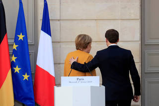FILE PHOTO: French President Emmanuel Macron and German Chancellor Angela Merkel leave after a joint news conference at the Elysee Palace in Paris