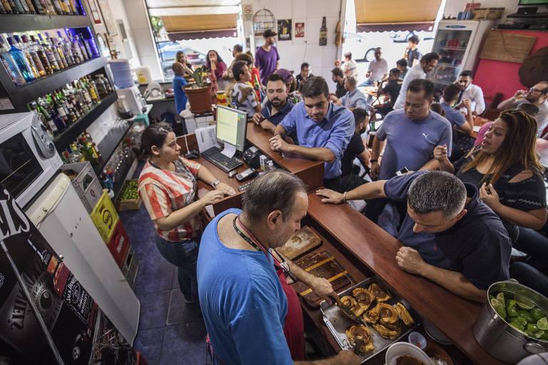 Clientes se aglomeram no balcão para pedir o torresmo especial de rolo, vendido no Buteko Ze do Breju, do comerciante Valter Baldo, em São Caetano do Sul (ABC)