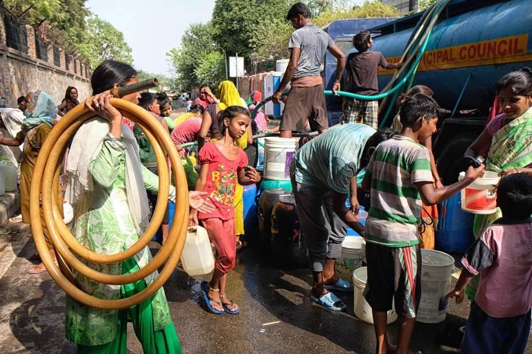 Moradores de Nova Déli coletam água potável em um caminhão disponibilizado pelo governo