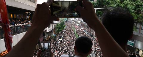 People take photos from an elevated walkway as thousands of protesters dressed in black file past on the street below during a new rally against a controversial extradition law proposal in Hong Kong on June 16, 2019. - Tens of thousands of people rallied in central Hong Kong on June 16 as public anger seethed following unprecedented clashes between protesters and police over an extradition law, despite a climbdown by the city's embattled leader. (Photo by HECTOR RETAMAL / AFP) ORG XMIT: 3802