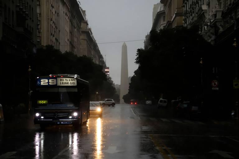 Ônibus e carro andam com farol ligado, em rua escura e com solo molhado
