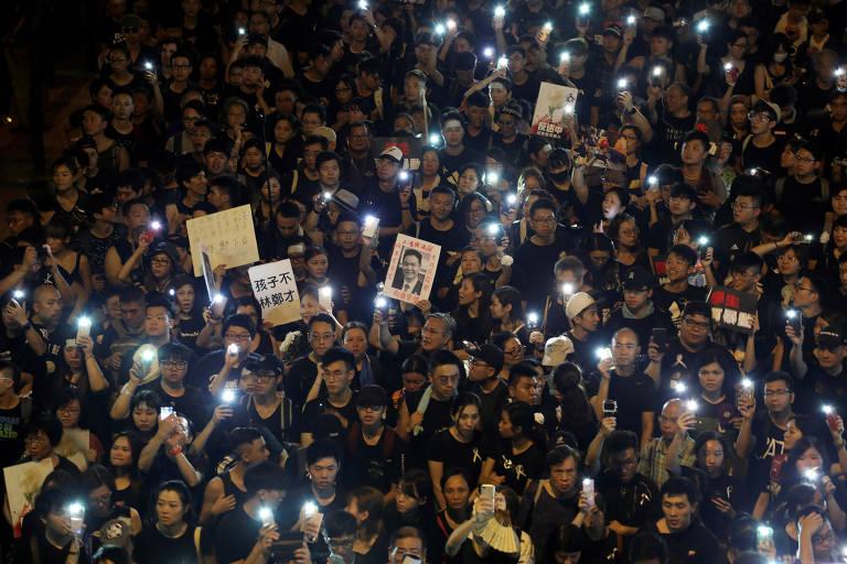 Manifestantes acendem luzes de celulares e seguram cartazes