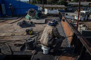 Funcionário trabalha na manutenção de balsa no estaleiro estadual em Guarujá (SP)
