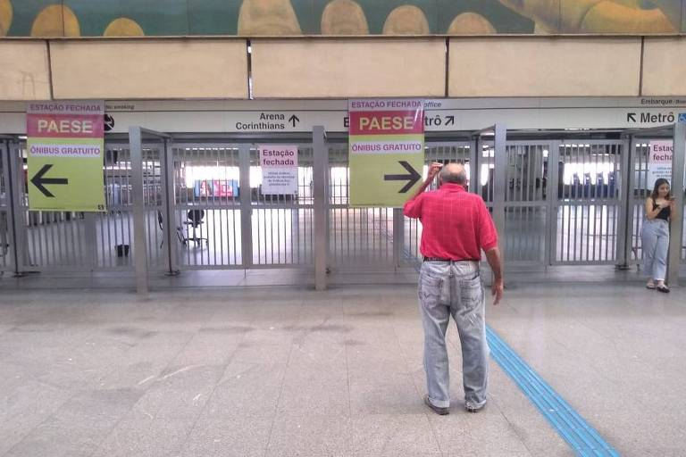 Passageiro observa portão da estação Corinthians-Itaquera, da linha 3-vermelha do metrô, fechado neste domingo (16)